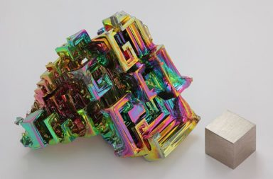 The chemical element bismuth as a synthetic made crystal. The iridescent surface is a very thin layer of oxidation. Beside it is a high purity (99.99 %) 1 cm3 bismuth cube for comparison. By Alchemist-hp