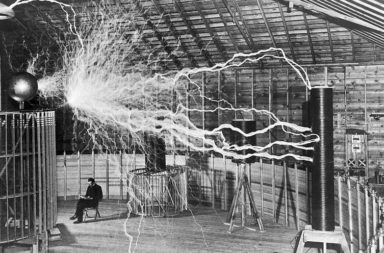 "Nikola Tesla sitting in his Colorado Springs laboratory next to his huge ""magnifying transmitter"" Tesla coil which is producing 22 foot bolts of electricity"